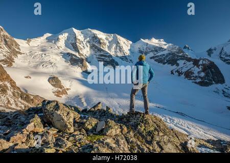 Hiker looking to Piz Palu from Diavolezza. Berniner Alps, Graubunden, Switzerland. - Stock Photo