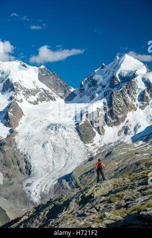 Hiker beneath Piz Bernina and Piz Rosbeg. Fuorcla Surlej, Silvaplana, Berniner Alps, Graubunden, Switzerland. - Stock Photo