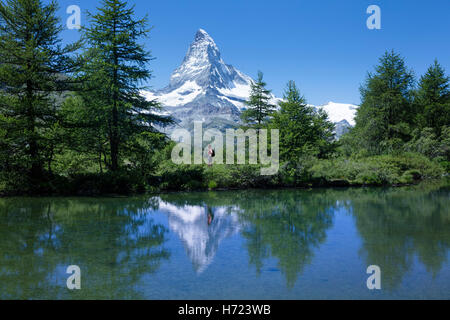 Hiker and Matterhorn reflected in the Grunsee, Zermatt, Pennine Alps, Valais, Switzerland. - Stock Photo