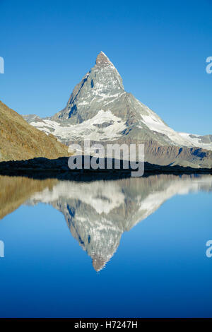 The Matterhorn reflected in the Riffelsee, Zermatt, Pennine Alps, Valais, Switzerland. - Stock Photo