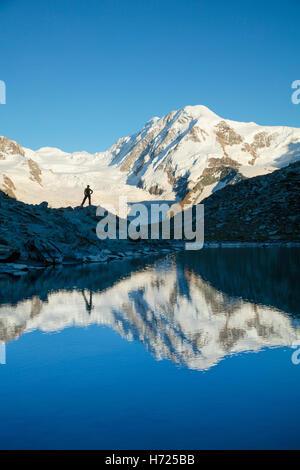 Hiker and Lyskamm reflected in the Riffelsee, Zermatt, Pennine Alps, Valais, Switzerland. - Stock Photo