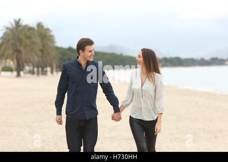 Couple in love taking a walk on the beach - Stock Photo