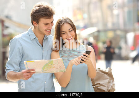 Couple of tourists consulting a city guide and smartphone gps - Stock Photo