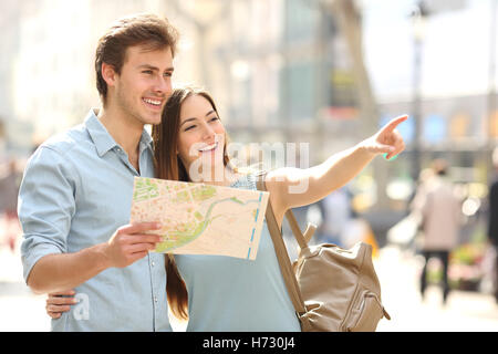 Couple of tourists consulting a city guide searching locations - Stock Photo