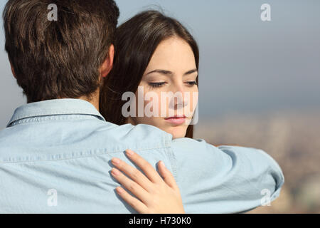 Sad woman hugging her boyfriend couple problems - Stock Photo