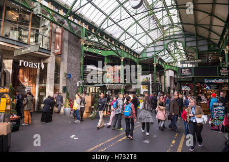 LONDON - OCTOBER 31, 2016: Visitors browse the specialty food stalls at Borough Market, one of the largest and oldest - Stock Photo