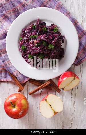 braised red cabbage with apples and cinnamon close-up on the table. Vertical view from above - Stock Photo
