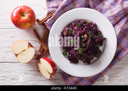 braised red cabbage with apples and cinnamon close-up on the table. horizontal view from above - Stock Photo