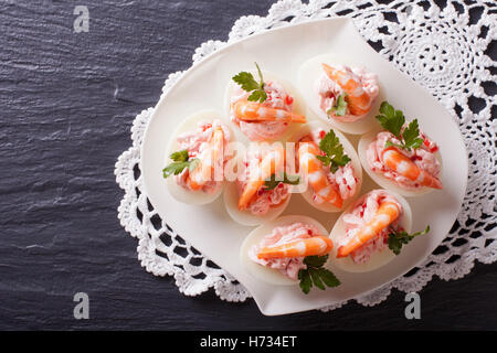 eggs stuffed with shrimp on a plate on the table. horizontal view from above - Stock Photo