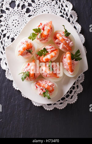 eggs stuffed with shrimp on a plate on the table. vertical view from above - Stock Photo