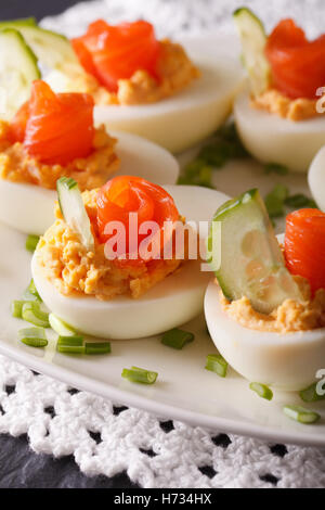 Beautiful food: Eggs stuffed with salmon and cucumber closeup on a plate. vertical - Stock Photo