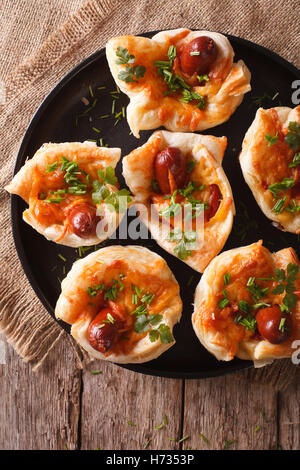 Tasty muffins with sausage and cheese on a plate close-up. vertical top view - Stock Photo
