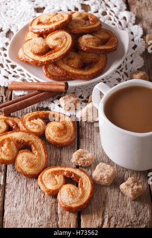Coffee with milk and cookies Palmiers close-up on the table. Vertical - Stock Photo