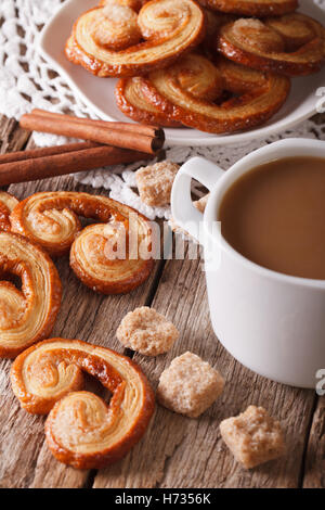 cookies of puff pastry Palmiers and coffee with milk close-up on a table, vertical - Stock Photo