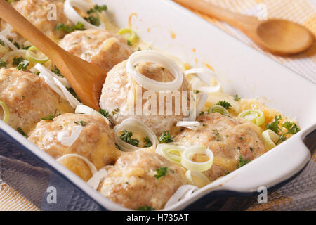 Tasty chicken balls baked in cheese cream sauce close-up in the dish for baking. horizontal - Stock Photo