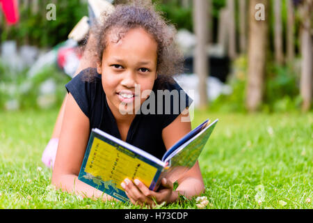 black girl reads book on meadow - Stock Photo