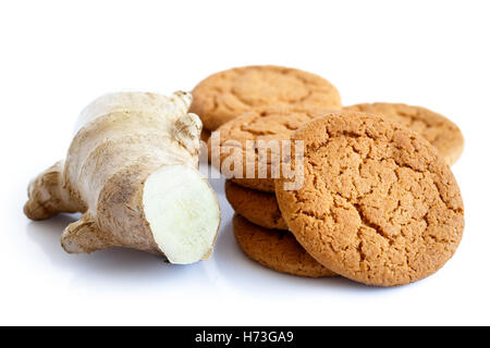 Fresh cut root ginger next to a pile of ginger biscuits isolated on white. - Stock Photo