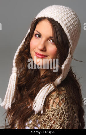 Pretty young woman with long hair wearing a crochet hat and cape - Stock Photo