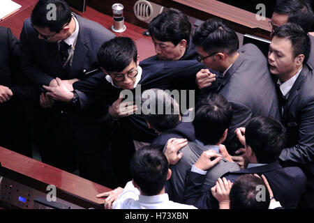 Hong Kong security guards restrain newly elected lawmaker SIXTUS LEUNG after he tried to read out his Legislative - Stock Photo
