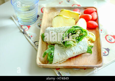 Fresh vegetable wrap with sliced tomato and apple on a tray - Stock Photo