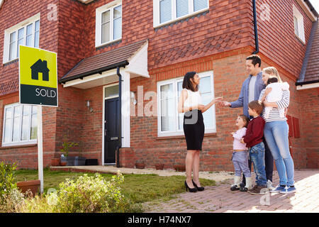 Young Family Collecting Keys To New Home From Realtor - Stock Photo