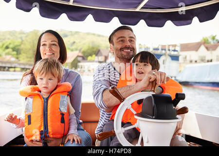Family Enjoying Day Out In Boat On River Together - Stock Photo