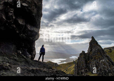 A woman stands at the base of the Old Man of Storr looking out to the Cuillin Hills on the Isle of Skye. - Stock Photo
