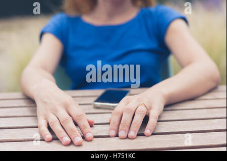 A young woman is sitting at at table outside and is using her smart phone on a summer day - Stock Photo