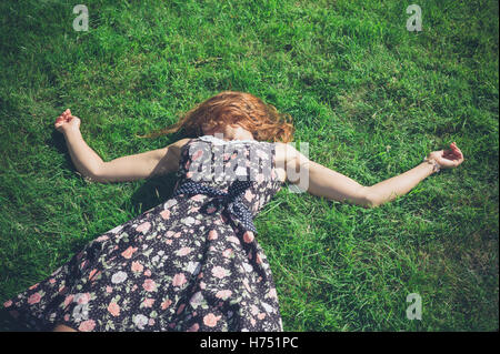 A young woman wearing a dress is lying in the green grass on a sunny summer day - Stock Photo