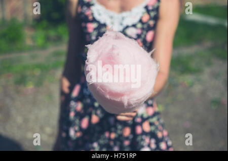 A young woman wearing a dress is standing outside with a candyfloss on a sunny summer day - Stock Photo