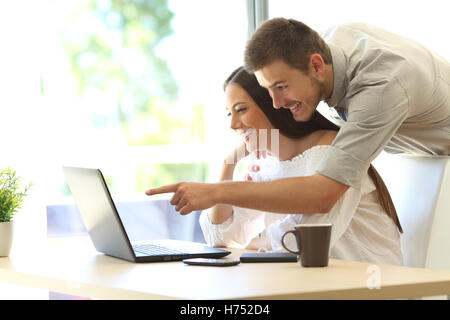 Side view of a happy couple searching information on line in a laptop on a table at home or hotel room with a window - Stock Photo