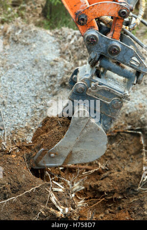 Closeup of an excavator digging soil from the ground. - Stock Photo