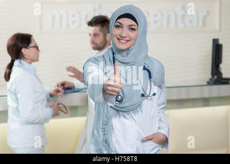 Happy smiling cheerful female muslim doctor with thumbs up gesture - Stock Photo
