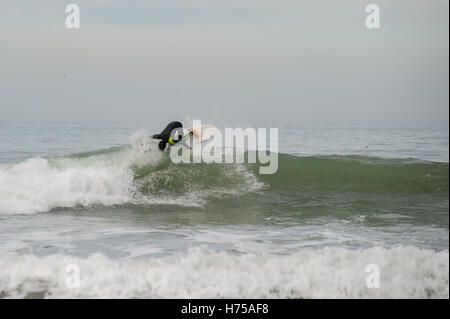Surfer hitting the lip at South Jetty in Ventura. - Stock Photo