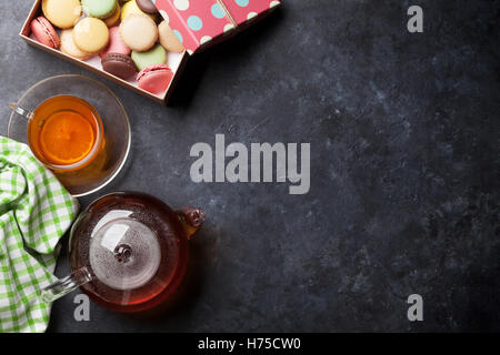 Tea cup, teapot and macaroons gift box on stone table. Top view with copy space - Stock Photo