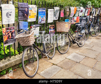 Cambridge bicycles leaning against a fence covered in posters, England, UK - Stock Photo