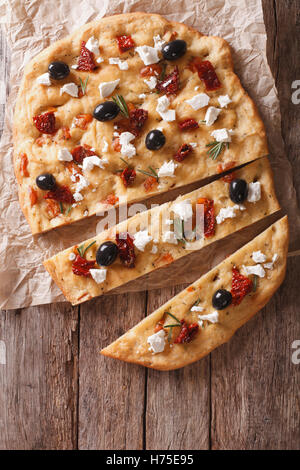 Focaccia with dried tomatoes, feta and olives on the table. vertical view from above - Stock Photo