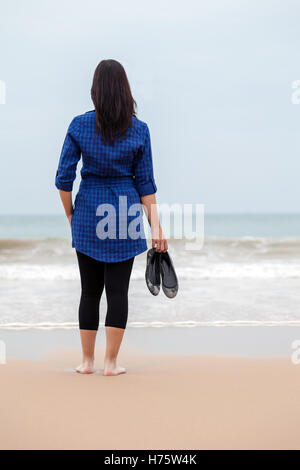 Lonely and depressed woman standing in front of the sea in a deserted beach on an Autumn day. - Stock Photo