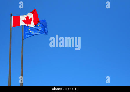 Canadian and European flags waving in the wind over blue sky (montage) - Stock Photo