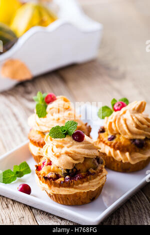 Homemade autumn cranberry pumpkin cupcakes with cream cheese icing on rustic wooden table - Stock Photo