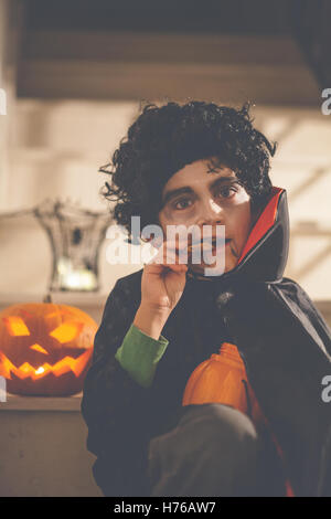 Boy dressed in Dracula Halloween costume eating a cookie - Stock Photo