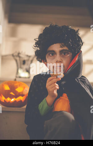 Boy dressed in Dracula Halloween costume holding a cookie - Stock Photo