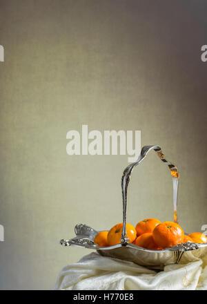 Antique silver fruit basket filled with mandarin oranges - Stock Photo