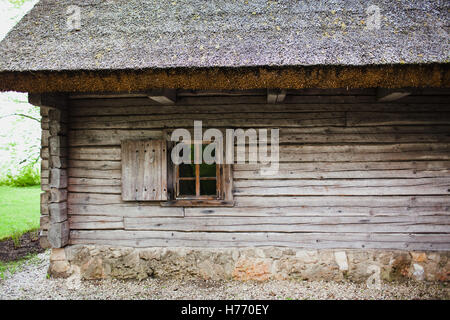 Old wooden house with thatched roof. - Stock Photo