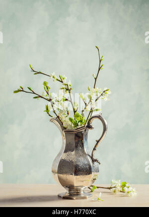 Antique silver jug filled with spring blossom - Stock Photo