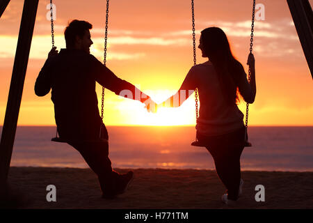 Back light portrait of a couple silhouette sitting on swing holding hands watching a sunrise on the beach with the - Stock Photo