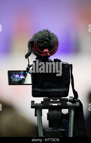 A digital slr video camera on a tripod with microphone recording video at an event - Stock Photo