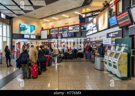 Passengers with baggage queueing up for check-in at the passenger terminal of Genova Cristoforo Colombo international - Stock Photo