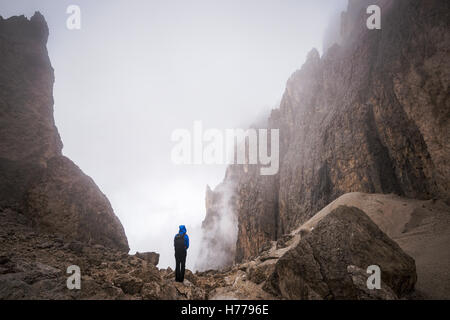 Young Woman standing in mountains, Dolomites, Val Gardena, South Tyrol, Italy - Stock Photo