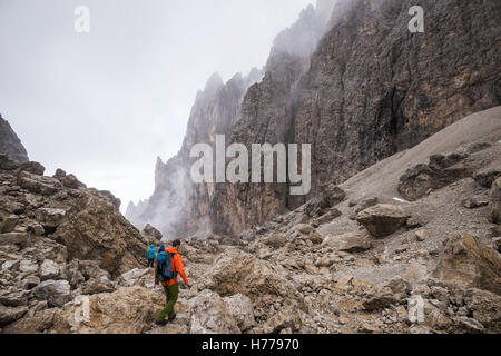 Three people hiking in the Dolomites, Val Gardena, South Tyrol, Italy